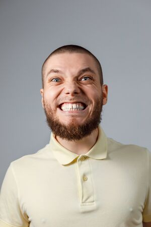 Close-up portrait of a young happy man in a yellow T-shirt, emotions on a gray background. isolated.