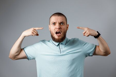 Portrait of a young man in a blue t-shirt angry shouting over a gray background. isolated.