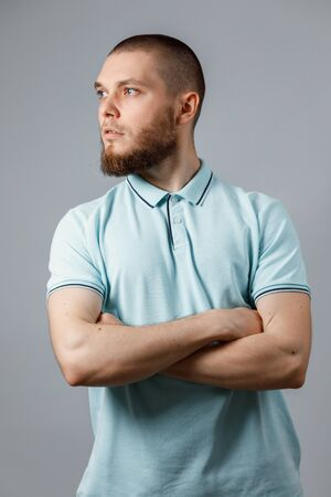 portrait of a young man in a blue t-shirt looking to the side on a gray background. isolated.