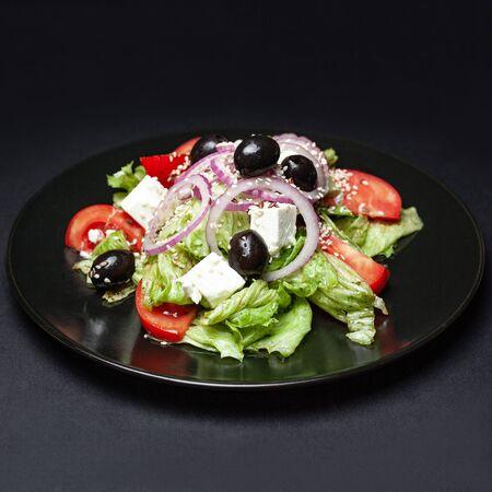 fresh greek salad on a black plate on a black background Фото со стока