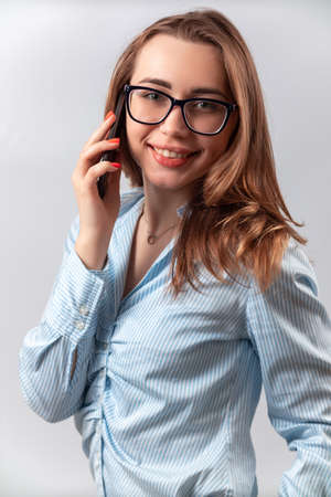 beautiful girl in a blue shirt and glasses talking on the phone on a white background. isolated