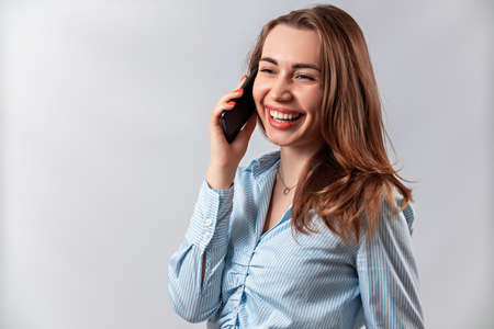 beautiful girl in a blue shirt talking on the phone on a white background. isolated Фото со стока