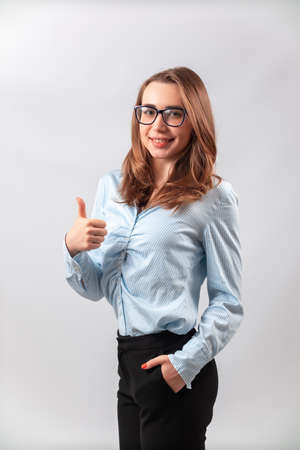 beautiful girl in a blue shirt shows class on a white background. isolated Фото со стока - 161874804