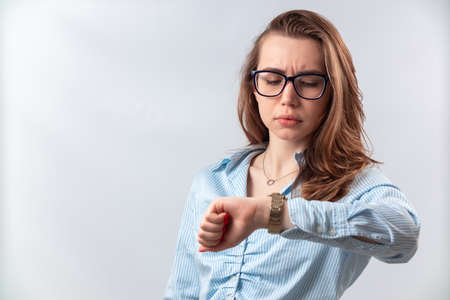 beautiful girl in a blue shirt and glasses looks at the clock on a white background. isolated Фото со стока