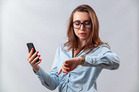 beautiful girl in glasses and a blue shirt looks at the watch on a white background. isolated Фото со стока