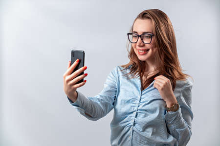beautiful girl in glasses and a blue shirt looks into the phone on a white background. isolated
