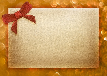 Blank gift tag tied with a bow of red satin ribbon. Natural texture photo