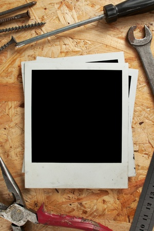 Old photo frames on wood background with a working tool photo