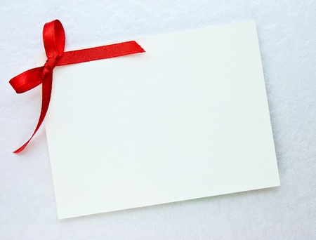 gift tag: Blank gift tag tied with a bow of red satin ribbon