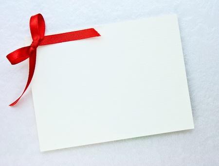 Etiqueta de regalo en blanco atado con un lazo de cinta de raso rojo Foto de archivo