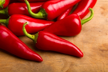 red chilli pepper plant: Red hot chili peppers on old wooden table Stock Photo