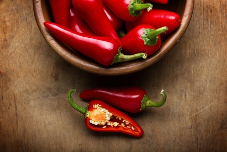 chili peppers: Red Hot Chili Peppers in bowl over wooden background