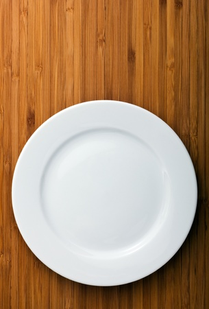 white plate: Empty white plate on wooden table