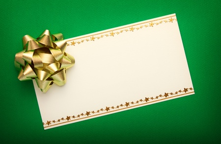 Greeting card on green paper with gold bow  photo