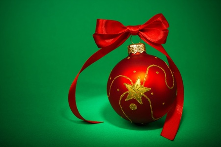 Red Christmas ball on green background photo