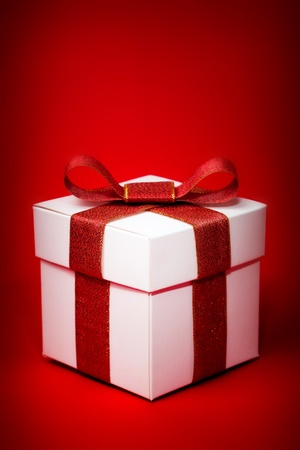 White box with a red ribbon on red background photo