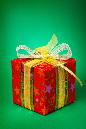 Gift with a gold ribbon on green background  photo
