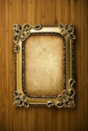 Gold frame with old paper on wood background photo