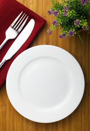 plate setting: white plate, knife and fork on wood table