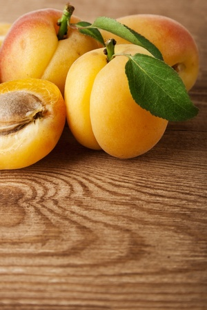 Fresh apricot with leaf on a wooden board photo
