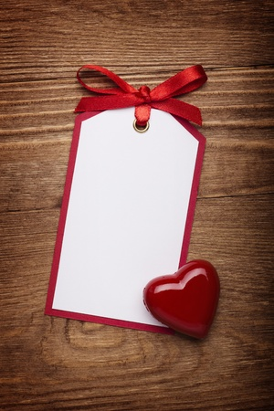 give: address card with bow and heart on old wooden background