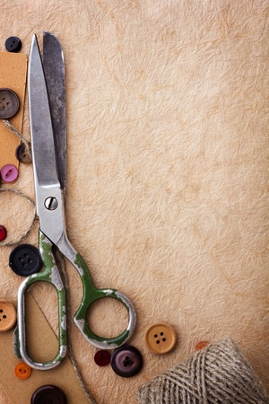 Old scissors and buttons on the paper texture photo