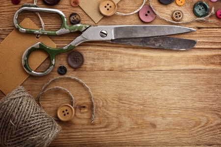 Old scissors and buttons on the wooden table  Stock Photo - 12770808