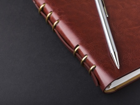 Notebook and pen in composition in black background Stock Photo - 12932647