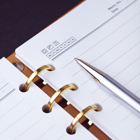 Open notebook with copper binding and stylish pen. photo