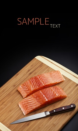salmon fillet with knife on wood board on black background photo