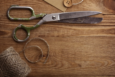 Old scissors and buttons on the wooden table Stock Photo - 12932507