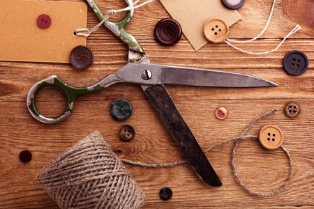 seam: Old scissors and buttons on the wooden table