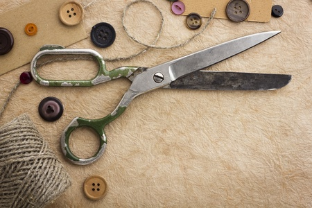 dressmaker: Old scissors and buttons on the paper texture