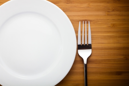 Empty plate and fork on wood table photo