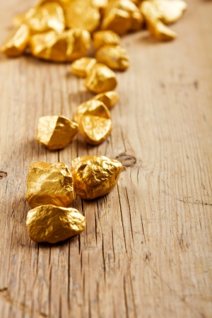 gold rush: gold nuggets on a wood background  closeup  Stock Photo