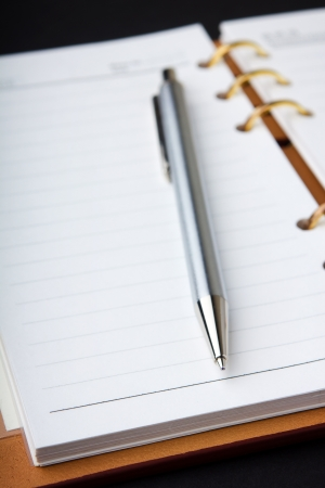 organizer page: notebook and pen on black background Stock Photo