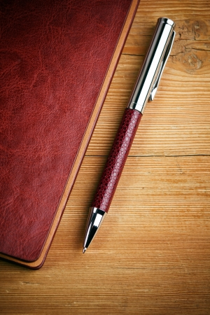 notebook and pen on wood background Imagens