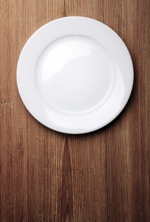 overhead: Empty white plate on wooden table