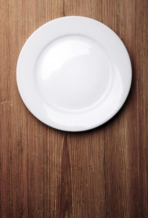 plato de comida: Vaciar la placa blanca en tabla de madera Foto de archivo