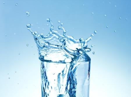 copa de agua: Cubos de hielo que salpican en el vidrio de agua