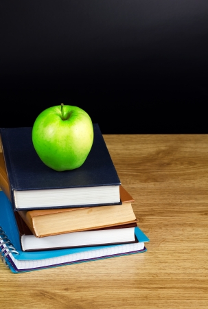Books and apple in wood table photo