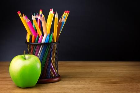 profesor alumno: L�pices y manzana sobre la mesa Foto de archivo
