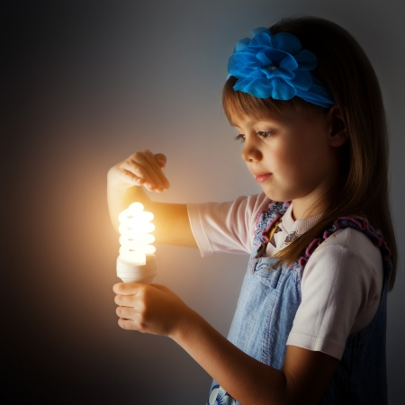 Little girl with a lit lamp in hand Imagens