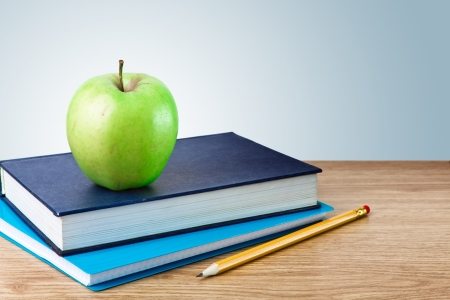 Book, notebook with apples and pencil on table