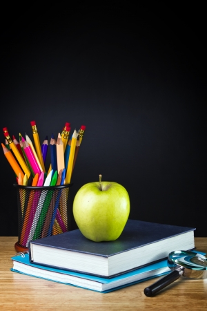 portrait orientation: Teachers desk with a color pencil, notebook and other equipment.