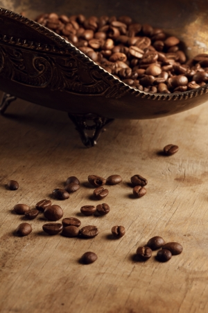 bronze bowl: coffee beans on a wood in a bronze bowl Stock Photo