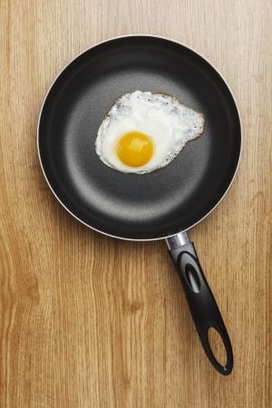 steel pan: Huevos fritos. Pan con mango de madera de fondo