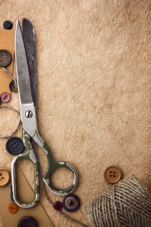 Old scissors and buttons on the paper photo