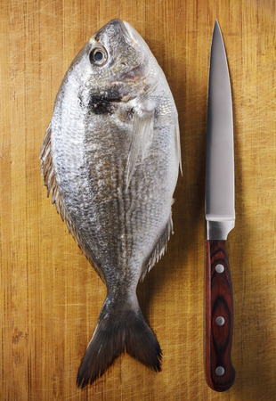 Fish with knife on textured wooden board photo