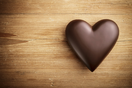 black heart: Chocolate heart on wooden background  Stock Photo